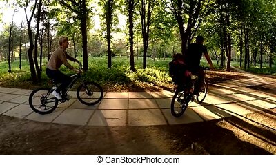 Happy People Riding Bicycles In Green Park At Sunny Day -...