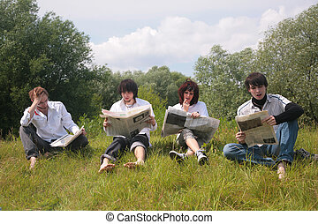 Four friends read newspapers on grass