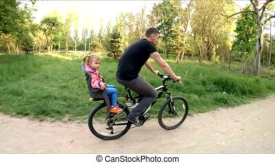 Man With Child On Backseat Riding A Bicycle In Park - SLOW...