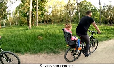 Young Family Riding Bicycles In Green Park - SLOW MO: Side...