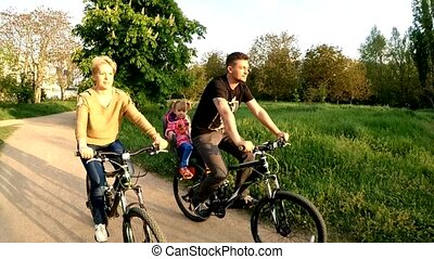 Young Family With Child Riding Bicycles In Green Park - SLOW...