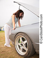 Woman looks under a car cowl