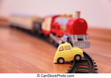 Red toy train and yellow toy car on railroad