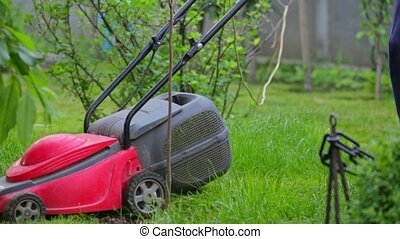 Senior Man Mowing Overgrown Lawn In His Yard - In the...