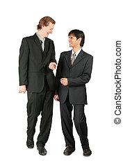 Two friendly businessmen walking