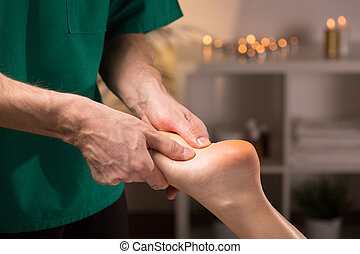 Male hands doing foot massage