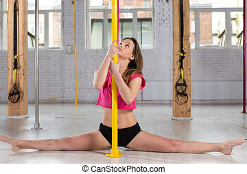 Pole dancer doing the splits - Young attractive female pole...