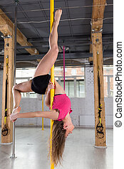 Girl performing pole dance - Young fit girl performing...