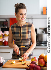 Woman smiling looking into distance while cutting apples -...
