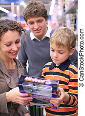 Boy with parents with toy in shop