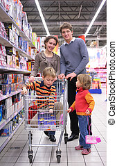 Family with son in cart in shop