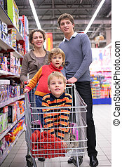 Family with children in cart in shop, focus on little girl
