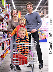 Parents with children in cart in shop, focus on little girl...