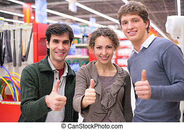 Three friends make gesture ok in shop