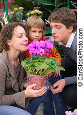 Parents and child with pot in flower shop, smell flower,...