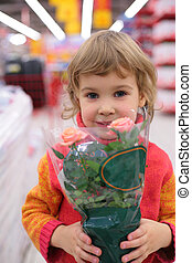 Child  holds pot with flower in shop