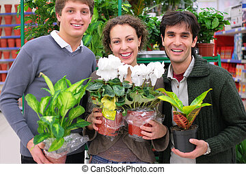 Three friends in shop holds pots with plants in shop, focus...