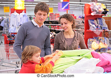 Parents with  child choose  fabric in shop