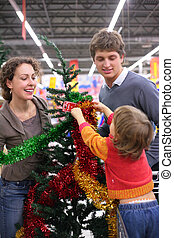 Parents with child  buys Christmas-tree with decorations