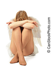girl in angels costume sits face in knees and having closed...