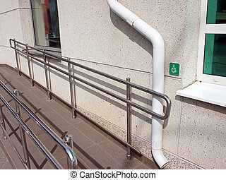 Ramp for physically challenged with metal railing at the...