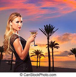 Blond girl sunset Arenal beach drinking vermout - Blond...