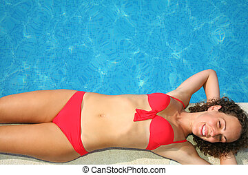 Young woman lies on back on edge of pond - Young woman lies...
