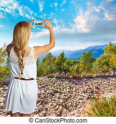 Blond tourist in Mallorca taking photos