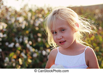 5 years old girl standing in the cotton field