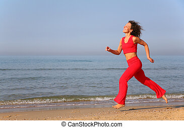 Young woman runs on shore of sea