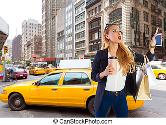 Blond shopping tourist girl calling a yellow Taxi NYC -...