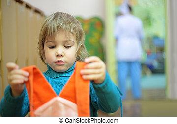 girl in kindergarten with dress in hands