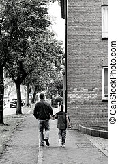 Father and son walking together in European city