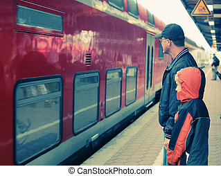 Father and 7 years old boy standing on a railway station and...