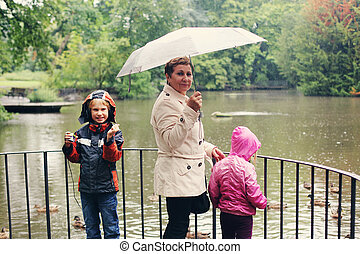 grandmother walking with kids in the rainy day