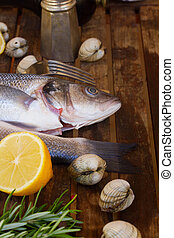 Seabass - Two Seabass silver raw fish with shellfish and...