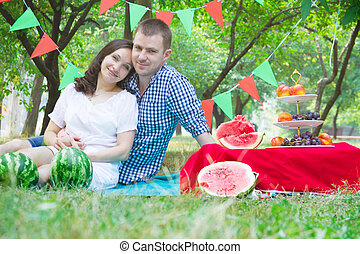 Couple on watermelon picnic in garden