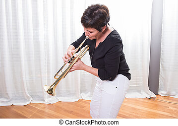 attractive woman playing the trumpet