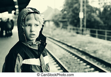 7 years old boy standing on a railway station and waiting...