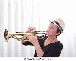 attractive woman with hat playing the trumpet