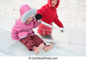 girl rolls down on ice slope with mother