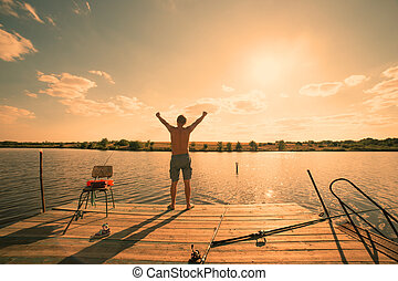 Happy man standing on pier with lake and sky in background, sunset warm light