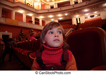 Little girl sits in theater