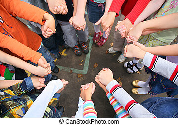 Circle from children, who are held for hands, kindergarten