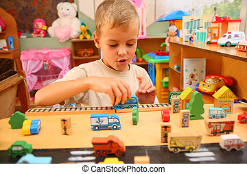 Boy plays with toy  in playroom