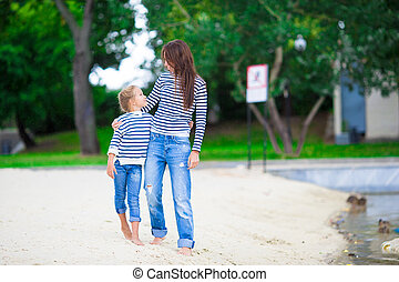 Happy mom and adorable little girl enjoying a walk along the...