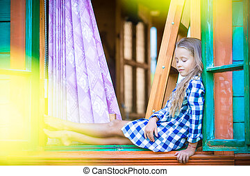 Adorable little girl in the window of rural house outdoors