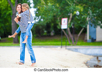 Happy mom and adorable little girl enjoying summer vacation...