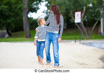 Young mother and adorable little girl enjoying a walk along...
