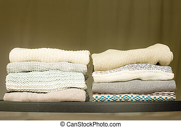 Two piles of warm sweaters for fall or winter on a shelf in a closet. Soft draped background.